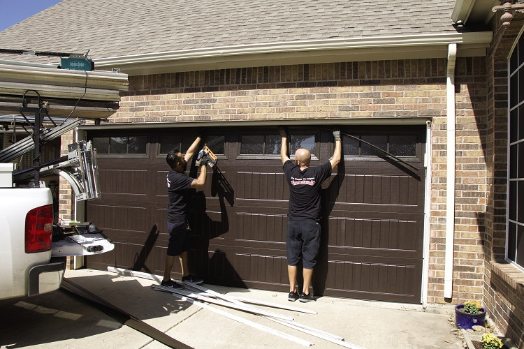 garage door experts fixing a door
